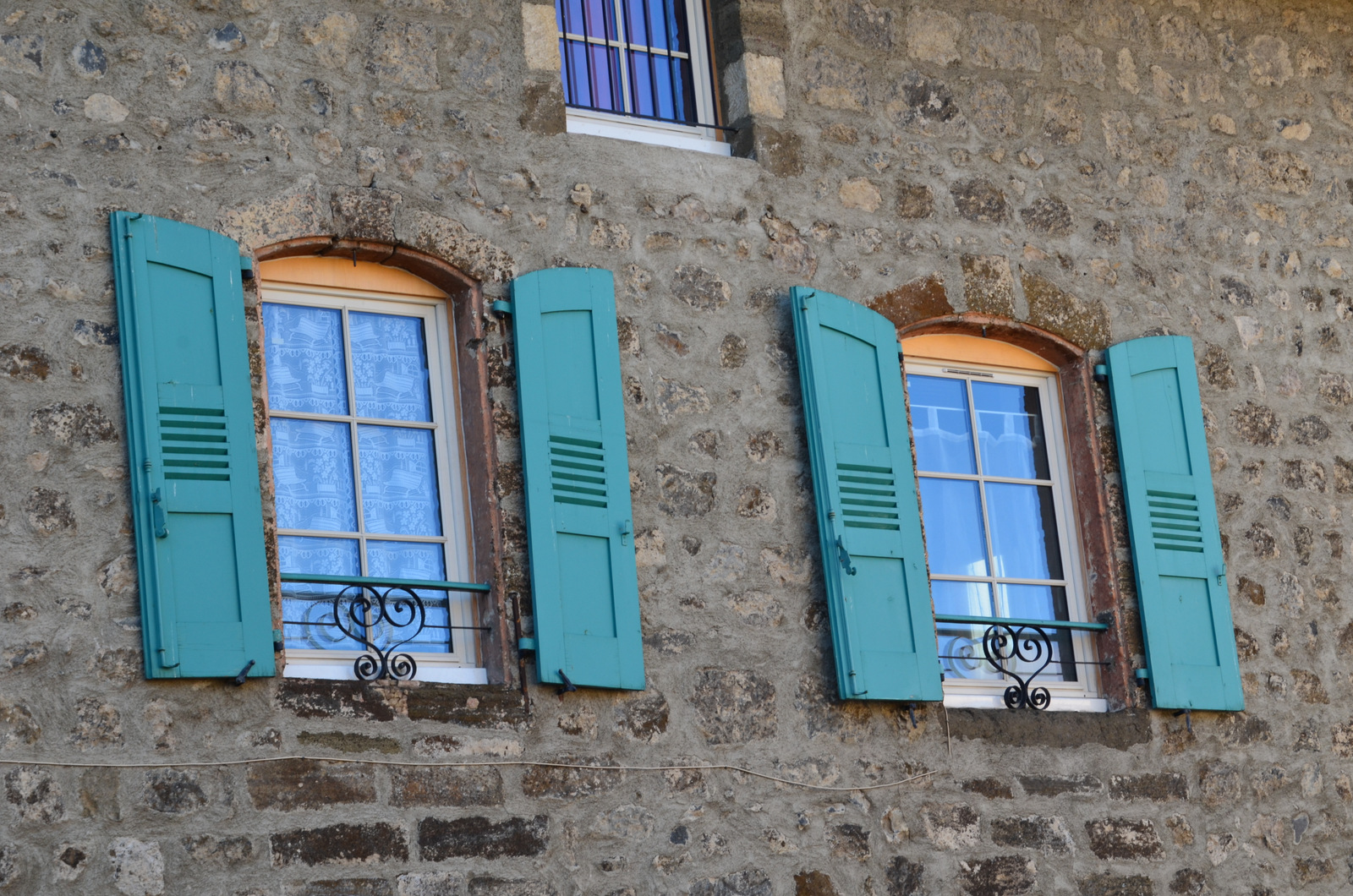 Seagreen shutters and heartshaped wrought iron on stone house. Charm!